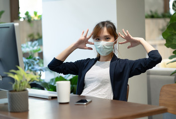 Portrait of young Asian woman prepare to wear medical disposable mask for protection flu and covid-19,corona virus and looking at camera in modern office. Covid-19 virus and Protection concept.