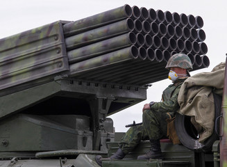 A serviceman of the self-proclaimed Donetsk People's Republic (DNR) sits on Grad multiple rocket launcher systems during military exercises at a target range outside the town of Horlivka (Gorlivka)
