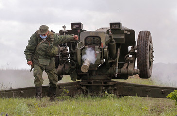 A serviceman of the self-proclaimed Donetsk People's Republic (DNR) fires howitzer during a military exercise at a target range outside the town of Horlivka (Gorlivka)