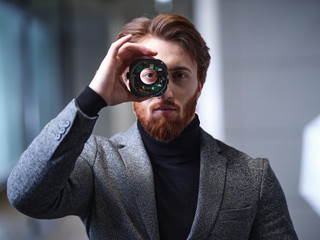 Portrait of businessman looking through an object in modern office