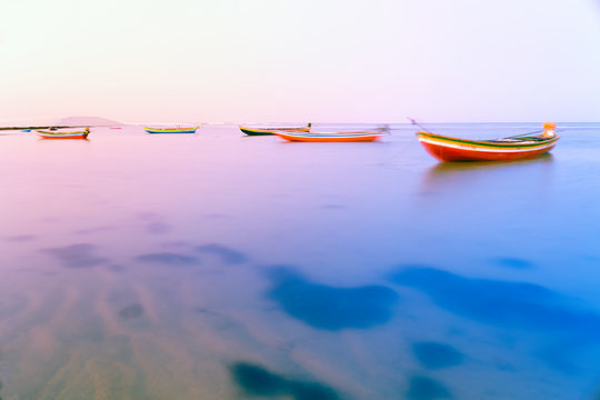 Fishing boats floating on the water of the Atlantic sea at sunset, Jericoacoara, Brazil
