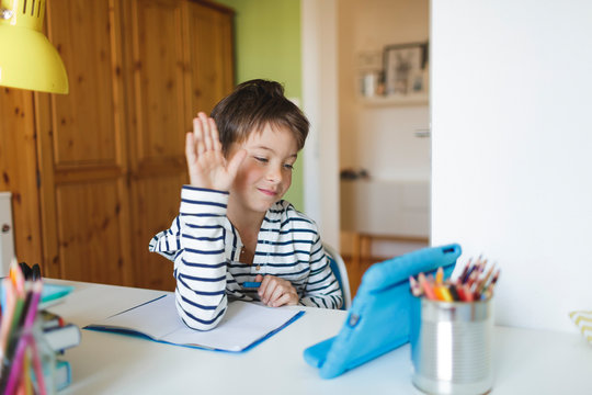 Boy doing homeschooling and using tablet at home
