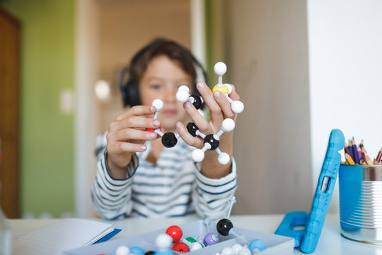 Boy doing homeschooling and holding molecule model, using tablet and headphones at home