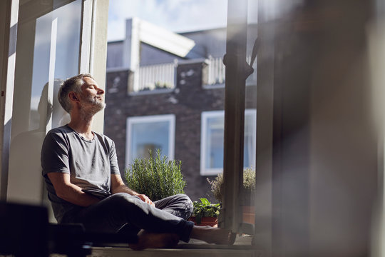 Mature man sitting at the window at home with closed eyes