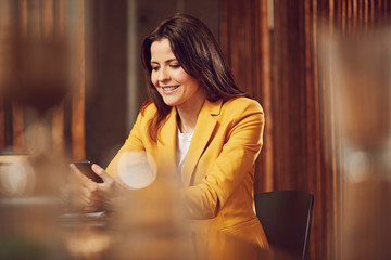 Smiling businesswoman wearing yellow suit sitting at desk in office using cell phone