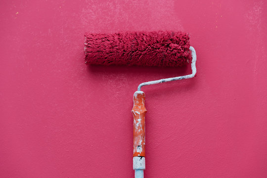 Studio shot of red paint roller against red background