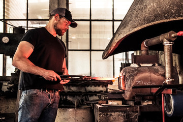 Knife maker working with damask steel at forging furnace