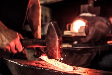 Knife maker at work, steel splinter during hammering damask steel
