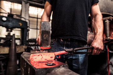 Knife maker working scattering borax over hot damask steel