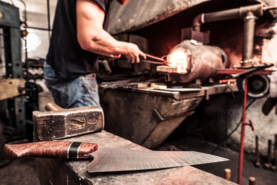 Knife maker working at melting furnace, finished knife on anvil in the foreground