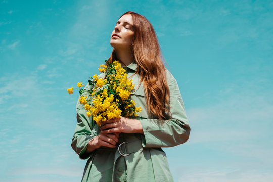 Portrait of redheaded young woman with eyes closed standing against sky holding bunch of yellow flowers