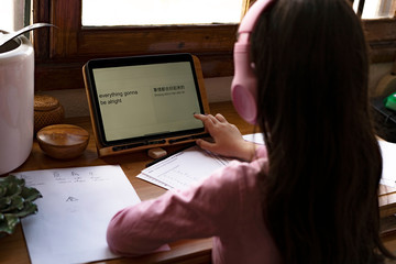 Girl wearing headphones translating languages on digital tablet while learning comics at home