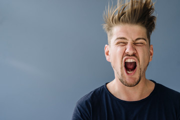 Portrait of a screaming man with tousled hair