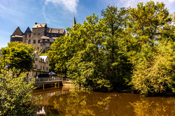 Limburg, Germany - 21st May 2020: A german photographer visiting the city, taking pictures of the castle behind the river Lahn at a sunny day in spring.