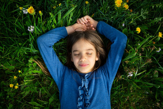 Portrait of girl with eyes closed relaxing on a meadow in spring