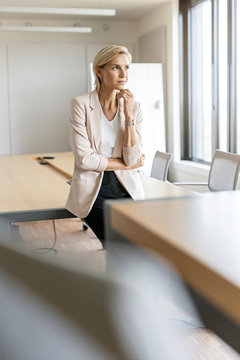 Blond businesswoman in conference room thinking