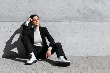 Young woman wearing black suit sitting on floor in front of concrete wall Wall mural
