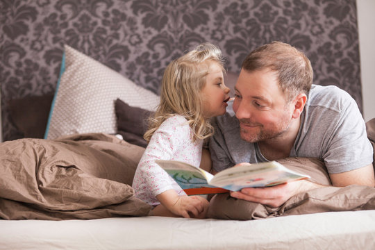 Father and daughter reading a book in bed, whispering in ear