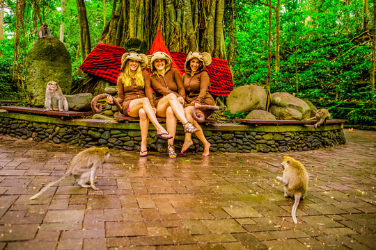 Women posing with the monkeys for a picture at the Sacred Monkey Forest, home to 700 monkeys, Ubud, Bali, Indonesia, Southeast Asia, Asia