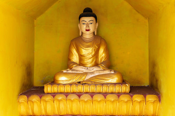 Spoed Fotobehang Historisch mon. A gold-coloured Buddha statue in a yellow alcove in a temple opposite to Shwezadi Monastery, Sittwe, Rakhine, Myanmar (Burma), Asia