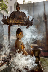 Spoed Fotobehang Historisch mon. A small Buddha statue at Sule pagoda, surrounded by clouds of smoke with two Kinaree statues visible in the background, Yangon (Rangoon), Myanmar (Burma), Asia