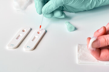 Express rapid COVID-19 test for detection of specific antibodies IgM and IgG to novel corona virus SARS-CoV-2 that cause Covid-19. Patient finger with cotton to stop blood after finger picking.