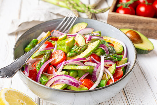 Healthy vegan meal, Juicy summer salad with blanched asparagus, cherry tomatoes, avocado slices and red onion, sprinkled with pepper and drizzled with olive oil and lemon juice