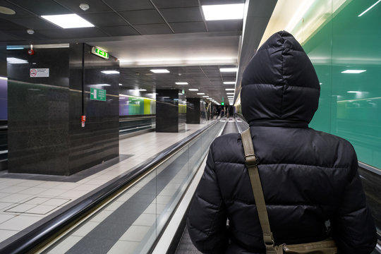 Rome, italy: a hooded back woman on a tapilurant inside the Rome Termini train station tunnel