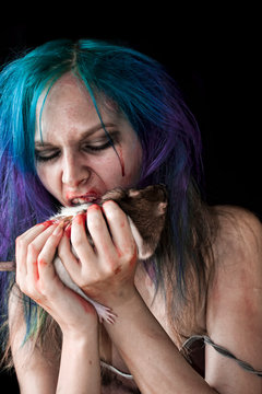 Close-up Of Spooky Woman Eating Rat Against Black Background