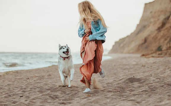 dog with girl running on the sea shore husky