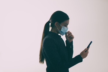 COVID-19 mask wearing woman touching her face while walking and texting mobile phone, Coronavirus...