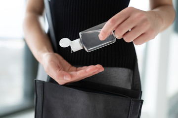 COVID-19 hand sanitizer woman using small portable sanitiser bottle on the go when going out...