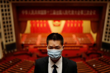Security member keeps watch at the end of the opening session of NPC in Beijing
