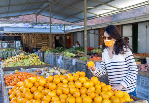 A young white woman with black hair shopping fruits in a street market wearing a protective mask during the coronavirus crisis