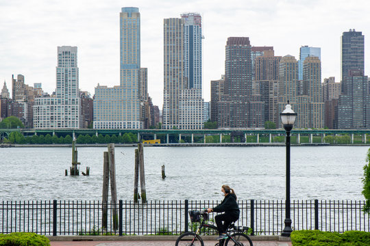 A New Jersey cyclist rides past the New York City Skyline while in quarantine
