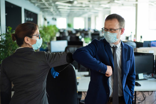 Office workers shake hands when meeting and greet bumping elbows. A new way to greet the obstructing spread of coronavirus. Man and woman in protective masks maintain a social distance at work.