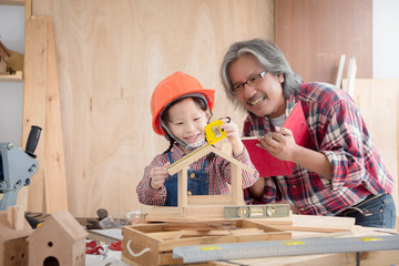 Senior male asian carpenter and grandchild making wooden bird house at home . Little asian girl...