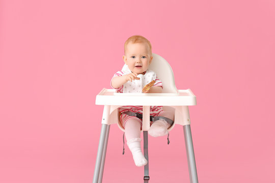 Cute little baby sitting in high-chair on color background