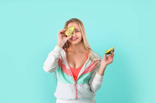 Young woman with avocado on color background. Diet concept