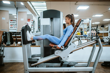 Fototapeta An attractive young caucasian girl in blue sports equipment on a leg machine in the gym
