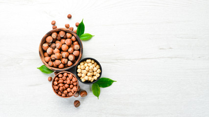 Hazelnuts in bowl on white wooden background. Nut. Wall mural