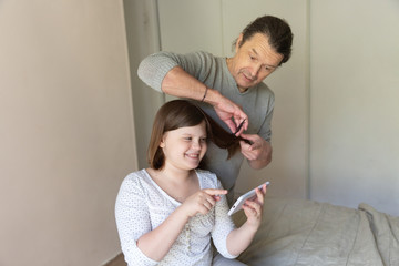 Caucasian dad learns to comb and trim daughter's hair online. Father cuts the hair of a child to...