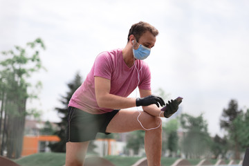 Sportsman with medical mask and gloves, smartphone and earbuds working out, jogging in urban surroundings.