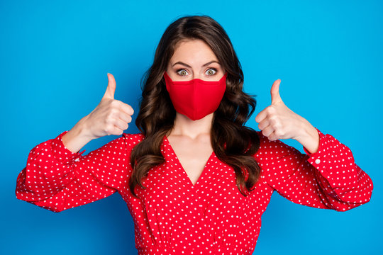Closeup photo of pretty lady raise thumb fingers up not take off face mask responsible citizen wear dotted red blouse dress protective facial mask isolated blue color background