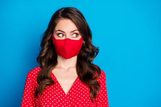 Closeup photo of pretty curly lady closed half face big eyes look side empty space wear dotted red blouse dress protective facial respiratory mask isolated blue color background