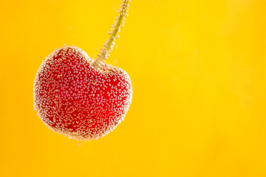 Close-up Of Wet Red Cherry Against Yellow Background