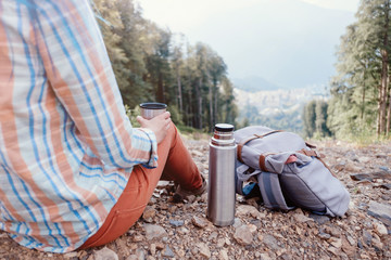 Backpacker woman resting with cup of tea in mountains.