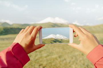 Hiker woman taking a photo mountain Elbrus with smartphone.