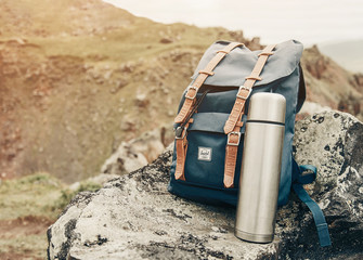 Kislovodsk, Elbrus region, Russia, 25 August 2017: Backpack Herschel and stainless thermos on stone in front of mountains on nature outdoor.