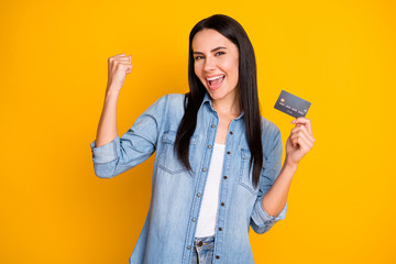Close-up portrait of nice attractive lovely pretty cute cheerful cheery girl holding in hand cell plastic card new solution novelty advert isolated bright vivid shine vibrant yellow color background